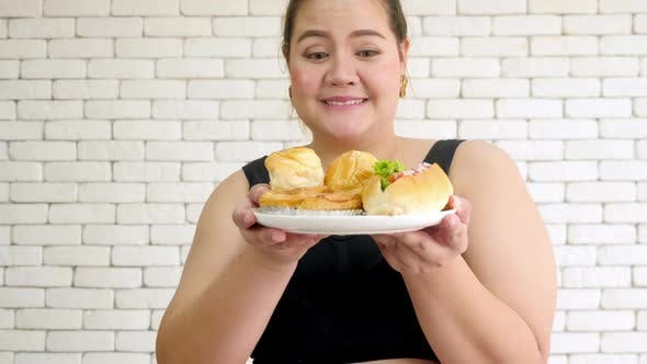 Overweight young woman in sportswear holding hot dog and buns