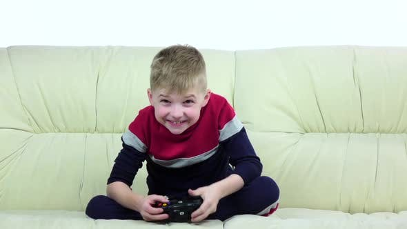 Boy with Games Console Playing Game on Couch, Slow Motion