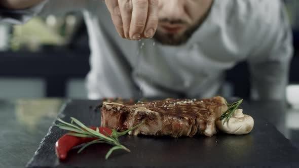 Thumbnail for Chef Salt Frittierfleisch in der Grillplatte. Closeup Man Hands Salzsteak in Zeitlupe