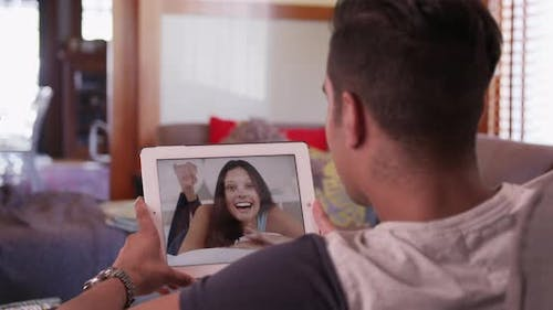 Millennial man video chatting or having a facetime conversation with his girlfriend on tablet comput