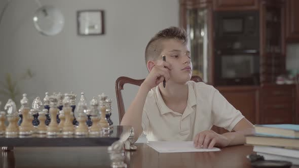 Thumbnail for Portrait of a Pensive Little Boy Sitting at the Table at Home. The Guy Is Holding a Pen Thinking