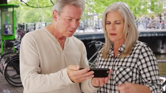 Thumbnail for Couple of elderly Caucasian people reading directions on smartphone device