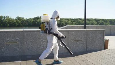 Young Sanitation Worker in Hazmat with Pressure Washer Outdoors