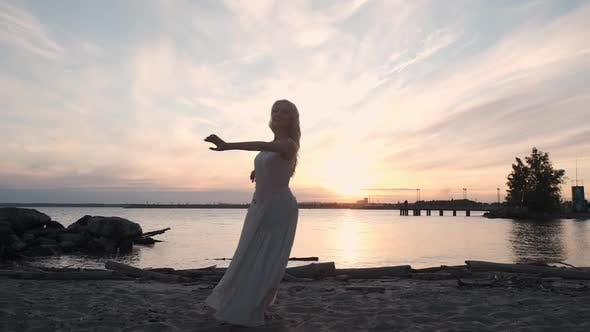 Thumbnail for Girl in a Flowing Dress Dancing By the Sea at Sunset