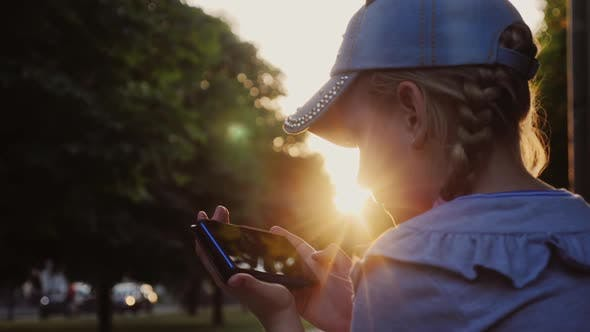 Thumbnail for Girl Sitting in the Park in the Evening at Sunset, Plays on the Smartphone