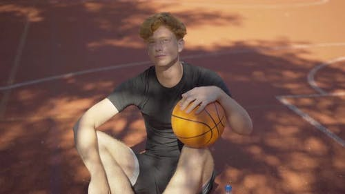 Exhausted Perspiring Redhead Sportsman Sitting with Ball on Outdoor Court and Looking Up at Sunlight