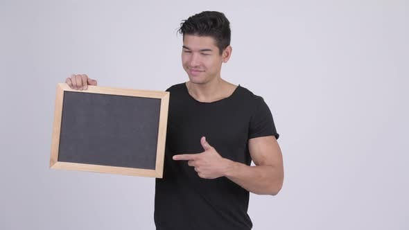 Thumbnail for Young Happy Multi-ethnic Man Holding Blackboard and Giving Thumbs Up