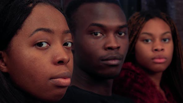 Thumbnail for Three African Friends Together Look To Camera with Serious Face in Living Room Detail of Faces