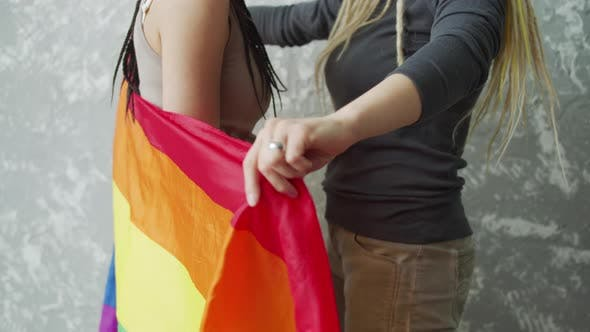 A Girl Covers Her Girlfriend By a LGBTQ Flag and Then Pulls to Herself