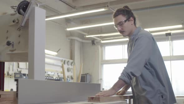 Thumbnail for Caucasian Woodworker Smoothing Wood Board on Jointer at Workshop