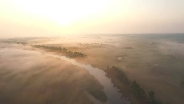 Thumbnail for Aerial Shot of Beautiful Endless Meadow Covering with Fog at Sunrise Time. Amazing Scenic View on