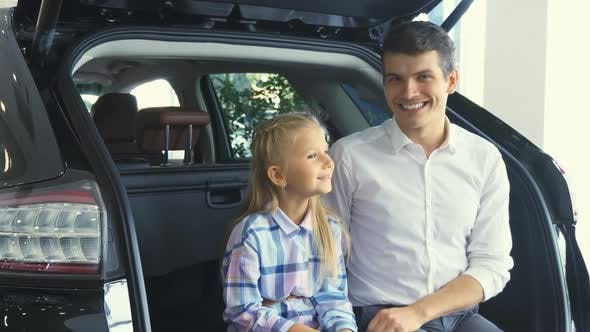 Thumbnail for Lovely Father and Daughter Are Sitting on the Open Trunk of the Car