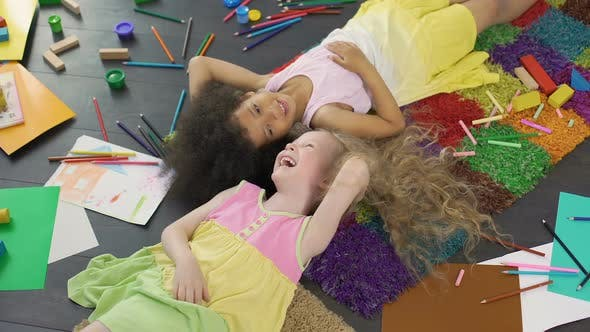 Thumbnail for Two multiracial female children lying on carpet and laughing, happy childhood