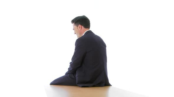 Thumbnail for Businessman sitting at edge of table looking over shoulder