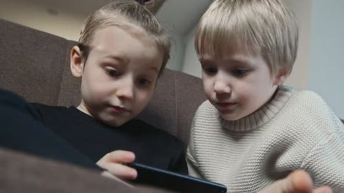 Two Brothers Play Game with Mobile Smartphone at Home
