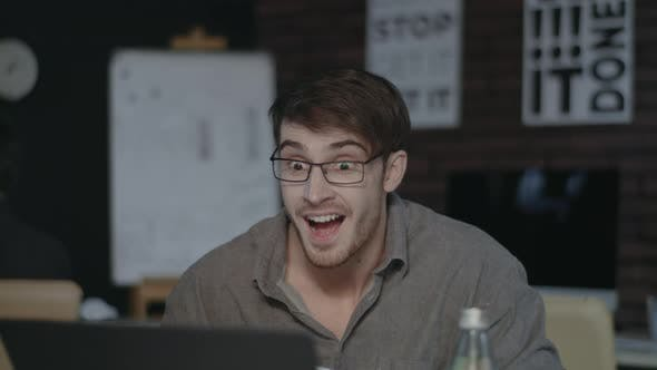 Thumbnail for Surprised Business Man Celebrating Good Results in Front of Laptop in Office.