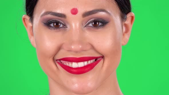 Thumbnail for Portrait of Beautiful Indian Girl Is Looking Seriously at the Camera and Then Smiling, Green Screen