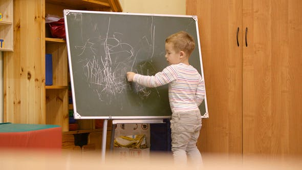 Thumbnail for Little Boy Drawing on A Chalkboard At Kindergarten
