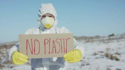 Man Wore in Protective Suit Holds No Plastic Sign on Abandoned Place in Winter
