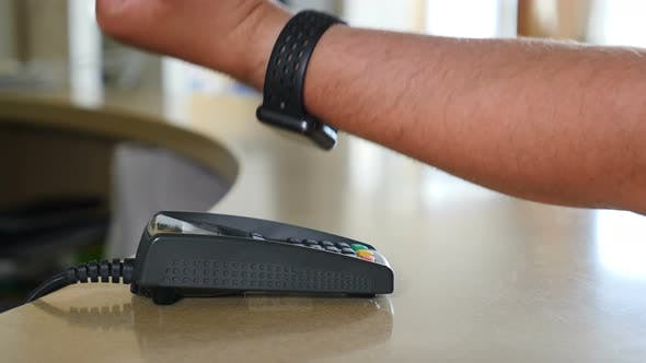 Barehanded Male Customer Paying with Smart Watch Using NFC Technology. Close-up. Contactless Payment
