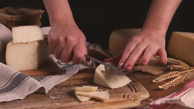 Women cut fresh homemade cheese on a wooden board with a cheese knife close up