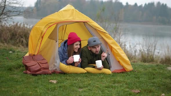 Thumbnail for Ouple Camps in der Natur mit Lagerfeuer und Getränken aus Vintage White Tassen