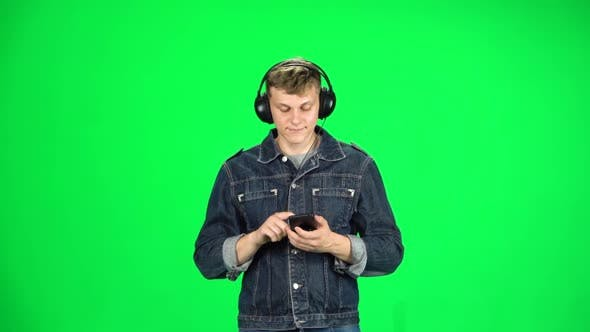 Male in Big Headphones Goes and Texting with Smartphone on Green Screen at Studio. Slow Motion