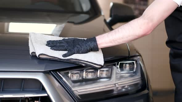 Thumbnail for Man Wipes a Car in a Garage