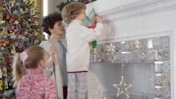 Thumbnail for Little Boy Decorating Fireplace for Christmas with Help of Mom and Sister