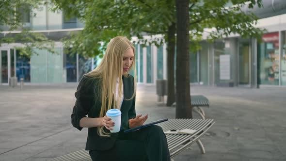 Thumbnail for Junge Geschäftsfrau mit Tablette und Kaffee trinken. Modernes Executive Girl im Anzug Sitzen auf