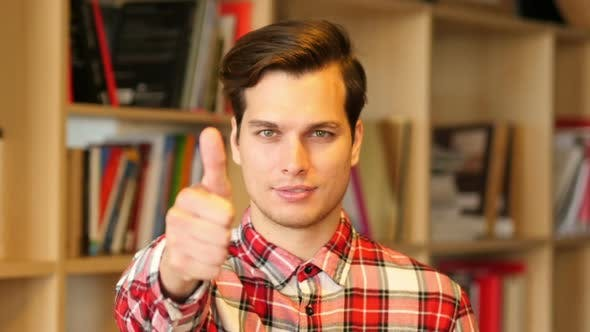 Cover Image for Thumbs Up Sign by Successful Young Man Indoor