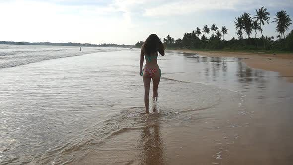 Slim Girl in Bikini Walks Over Sand in Shallow Waterline. Small Waves Splashes Over Legs of Young