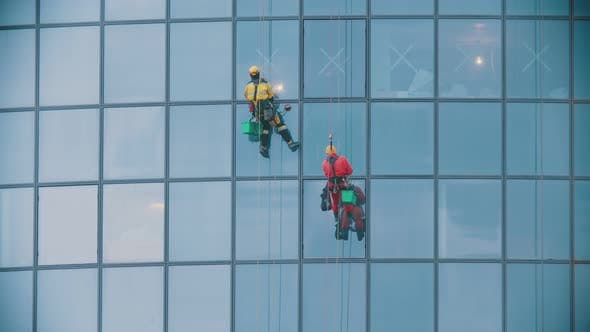 Thumbnail for Two Men Workers in Red and Yellow Work Clothes Cleaning the Exterior Windows of a Business