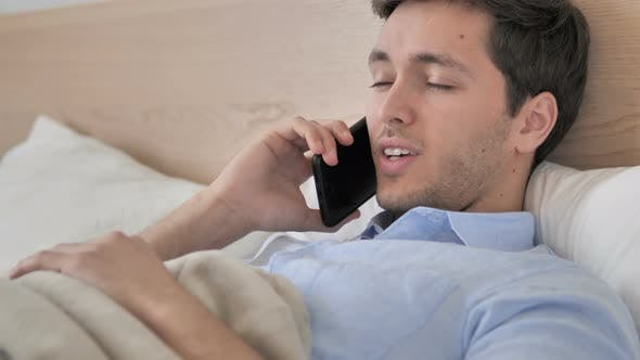 Thumbnail for Relaxing Young Man Talking on Phone in Bed