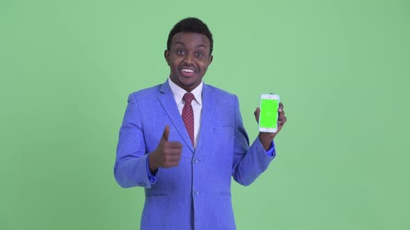 Thumbnail for Happy Young African Businessman Showing Phone and Giving Thumbs Up