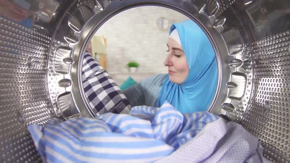Young Muslim Woman Takes Clean Laundry Out Washing Machine