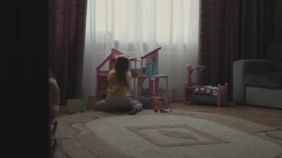 Little Girl in Pajamas Playing Alone in the Room