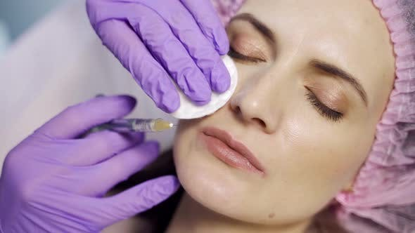 An Aesthetic Medicine Doctor Makes Botox to the Client's Lips