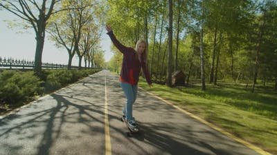 Pretty Female Skateboarder Enjoying Freedom and Leisure During Skateboarding