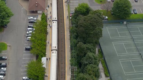 Aerial View of MTA Train Stopped at Station Near Tennis Courts in Long Island