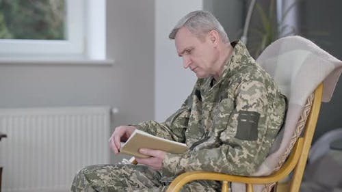 Side View of Concentrated Absorbed Middle Aged Man in Military Uniform Sitting on Rocking Chair
