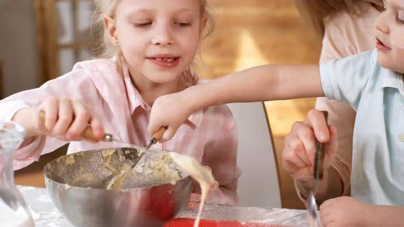 Young Caucasian Family Filling Cupcake Mold with Batter
