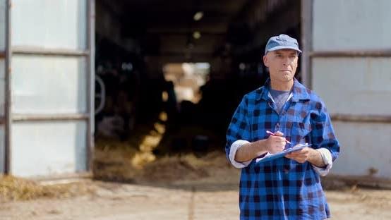 Thumbnail for Farmer Gesturing While Writing on Clipboard Against Barn