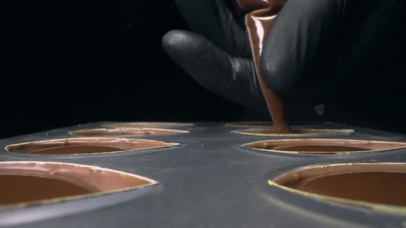 Thumbnail for Chocolatier Fills Chocolate Molds with Liquid Chocolate Filling for Praline Sweets