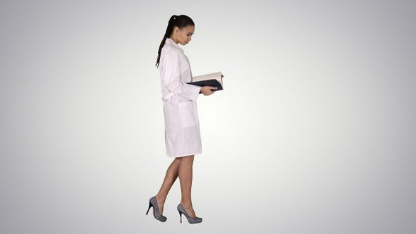 Cover Image for Attractive medicine student or doctor with notebook walking