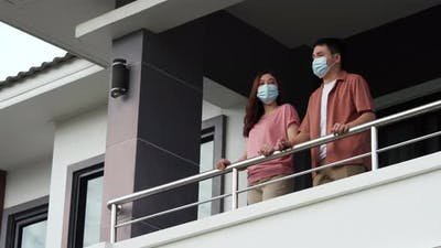 couple wearing a face mask and quarantine in balcony of the home