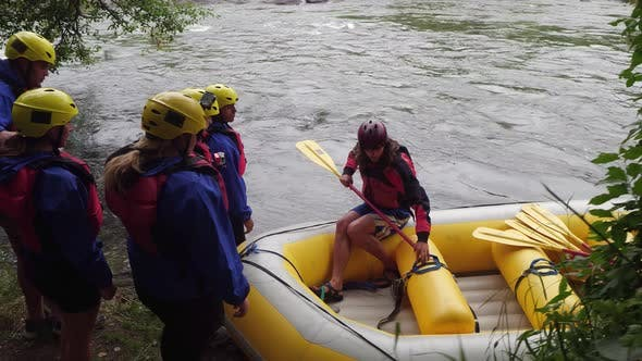 Thumbnail for Group of people white water rafting get instructions