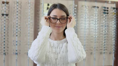 A Young Brunette with Blue Eyes in a Cozy White Sweater in an Optics Store Holds Glasses in Front of