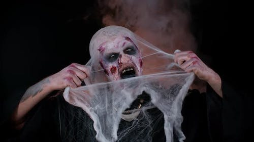 Scary Wounded Zombie Undead Guy Making Faces Hiding Through Spider Web Smiles Terribly Scares