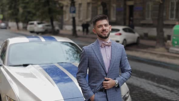 Thumbnail for Groom Near Sport Car on Street. Pink Shirt, Bow Tie, Blue Jacket